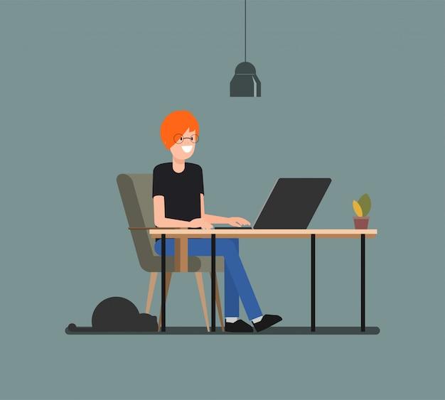 Junger mann, der mit computer im freiberufler mit einer katze arbeitet.