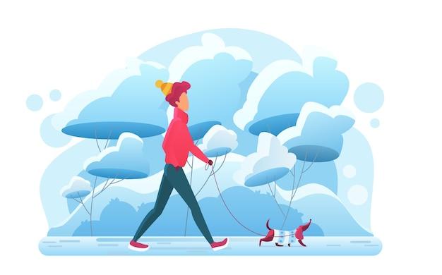 Junger mann, der mit hund im winterpark geht