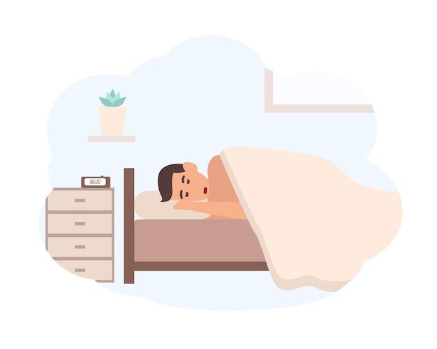 Junger mann, der neben nachttisch mit elektronischem wecker darauf schläft