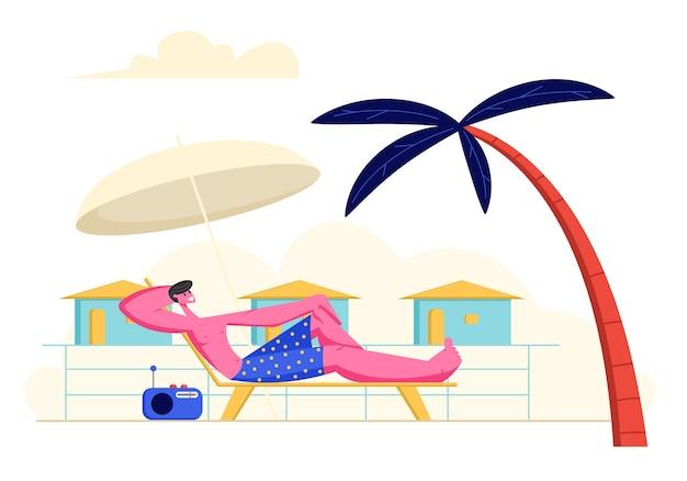 Junger mann faulenzen und hören radiomusik auf chaise lounge unter sonnenschirm und palme am meeresstrand bei sommerferien