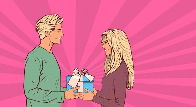 Junger mann geben der frauen-feiertags-geschenk-komischen retro- schönen paaren in der liebe geschenkbox