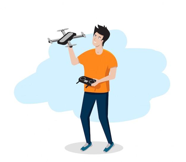 Junger mann hält eine drohne oder einen quadrocopter in seinen händen.