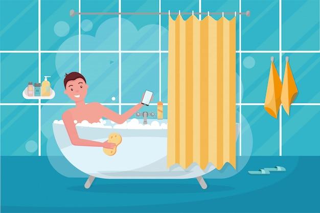 Junger mann im badewannenblasenschaum. badezimmerhauptinnenraum mit bad in der fliese mit duschvorhang. kerl, der waschlappen hält und smartphone verwendet