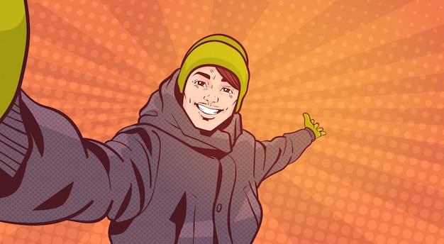 Junger mann in der winterkleidung nehmen selfie-foto, das hand zeigt, um raum über buntem retrostil-hintergrund zu kopieren