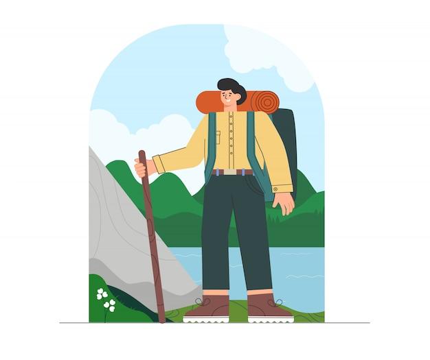 Junger mann in wanderkleidung und rucksack, stehend auf naturhintergrund