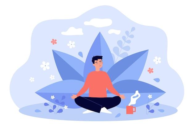 Junger mann mit tasse tee, der zwischen pflanzen und blumen meditiert
