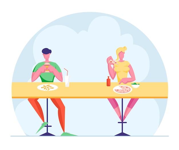 Junger mann und frau sitzen am schreibtisch auf hohen hockern, die fastfood im restaurant essen.