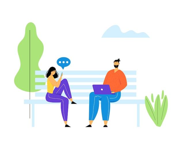 Junger mann und junge frau sitzen auf bank im park mit laptop und smartphone