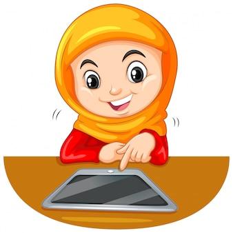 Junger moslemischer student, der eine tablette verwendet