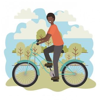 Junger schwarzer mann im fahrrad im park