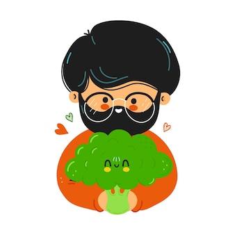 Junger süßer lustiger mann hält brokkoli in der hand