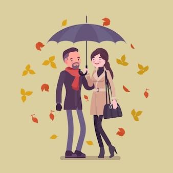 Junges glückliches paar mit regenschirm im herbst