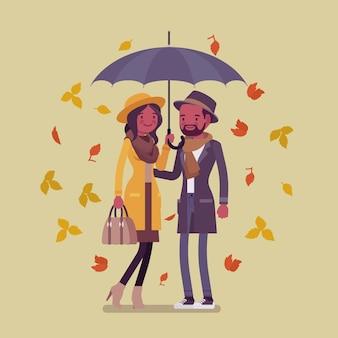 Junges glückliches schwarzes paar mit regenschirm im herbst