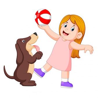 Junges mädchen, das ball mit hund spielt