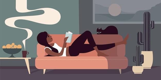 Junges mädchen liegt auf einem sofa mit einem buch und einer schwarzen katze. obst in einer vase und eine tasse kaffee in der nähe auf dem tisch.