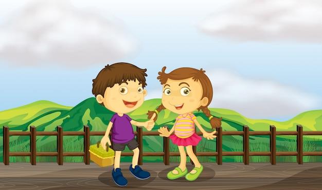 Junges mädchen und kleiner junge an der holzbrücke