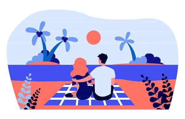 Junges paar, das sonnenuntergang am strand bewundert