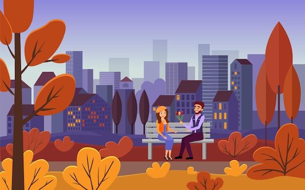 Junges paar, das zusammen auf einer bank in der freizeit der goldenen stadt des herbstes sitzt