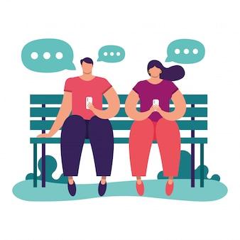 Junges paar mit smartphone in parkbank sitzen