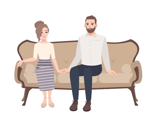 Junges paar sitzt auf elegantem sofa und hält hände