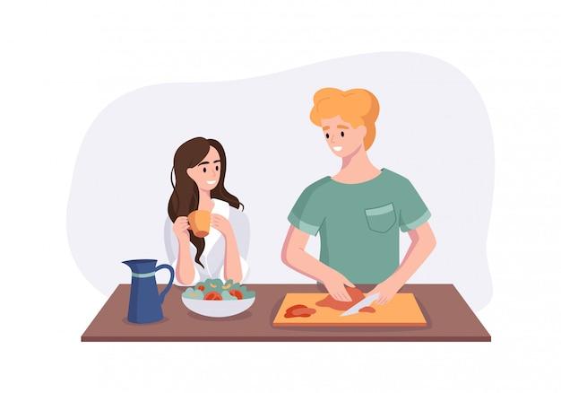 Junges paar spricht beim frühstück am esstisch in der küche. frau, die kaffee trinkt und mit ihrem ehemann spricht. mann, der mahlzeiten zu hause vorbereitet.