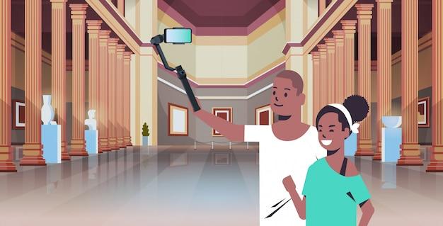 Junges paar unter verwendung des selfie-sticks, der foto auf smartphone-kameramann-frauenbesuchern im innenporträt der modernen kunstgalerie-museumshalle nimmt