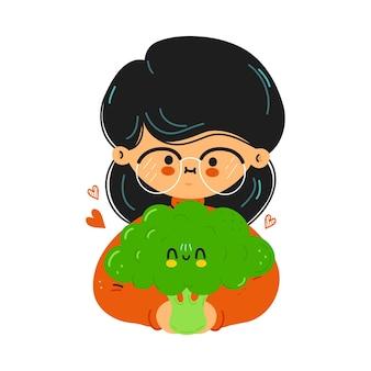 Junges süßes lustiges mädchen hält brokkoli in der hand