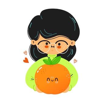 Junges süßes lustiges mädchen hält mandarine in der hand