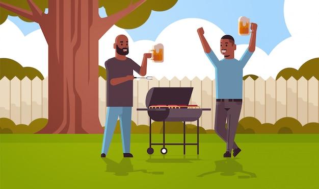 Jungs paar bereitet fleisch auf grill afroamerikaner männer trinken bier im freien freunde haben spaß hinterhof picknick barbecue party konzept flach in voller länge horizontal
