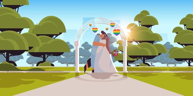 Jungvermähltes lesbisches paar mit blumen, die sich in der nähe des hochzeitsbogens küssen, transgender-liebe lgbt-community-hochzeitsfeier