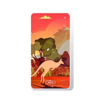 Känguru läuft von waldbränden in australien tiere, die in waldbrand buschfeuer brennende bäume naturkatastrophe konzept intensive orange flammen telefon bildschirm mobile app sterben