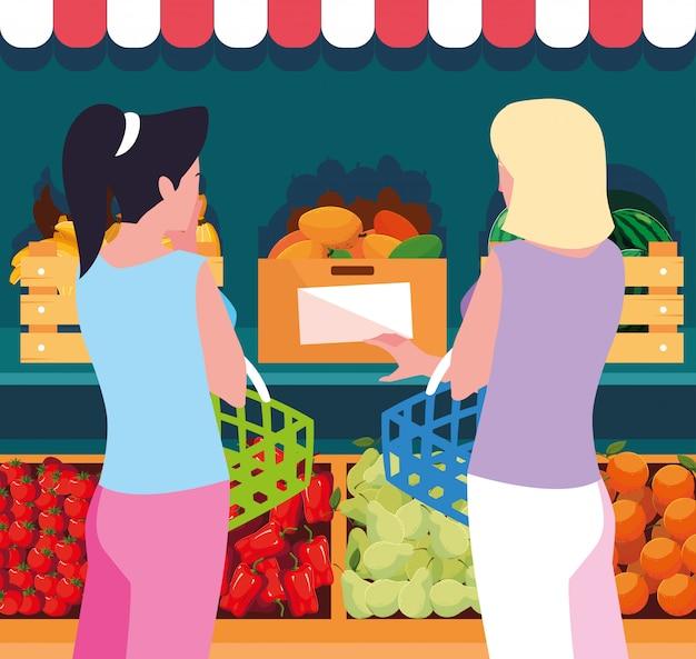 Käuferfrauen mit hölzernem speicher des schaukastens mit gemüse