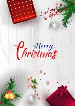 Kalligraphie von frohen weihnachten mit draufsicht von den geschenkboxen, von flitter, von kiefernblättern, von beere, von süßigkeit und von klingelglocke verziert auf weißem hölzernem.