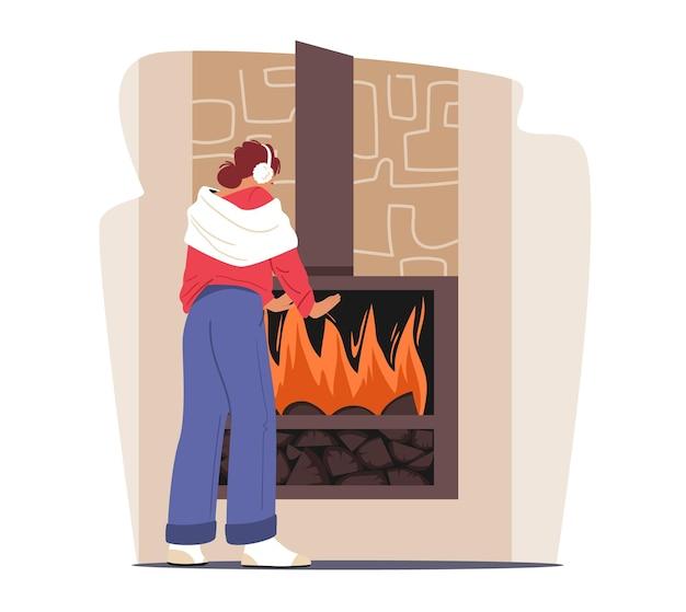 Kalte niedrige temperatur zu hause konzept. einfrierender weiblicher charakter, eingehüllt in warme kleidung, warme hände am brennenden kamin. kalter winter- oder herbstwetterfrost. cartoon-vektor-illustration