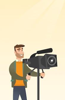 Kameramann mit einer filmkamera auf stativ.