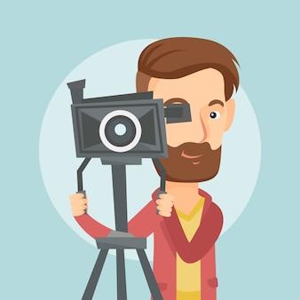 Kameramann mit filmkamera auf stativ.