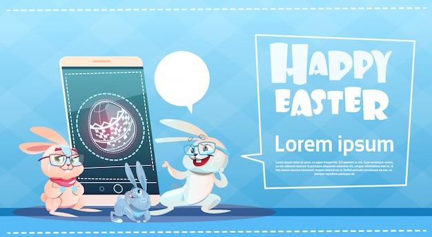 Kaninchen-gruppen-gebrauch-zell-intelligentes telefon-ostern-feiertags-symbol-gruß-karte