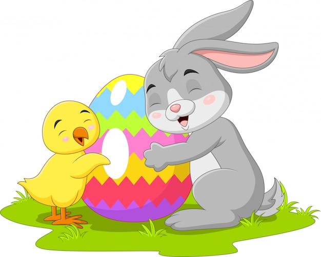 Karikatur kleines kaninchen mit küken und osterei