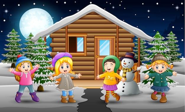 Karikatur von den glücklichen kindern, die einen winter tragen, kleidet vor dem schneienden dorf