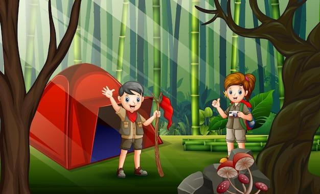 Karikaturillustration der pfadfinder, die draußen im bambuswald kampieren