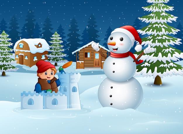 Karikaturjunge in der winterkleidung, die eine schneefestung errichtet