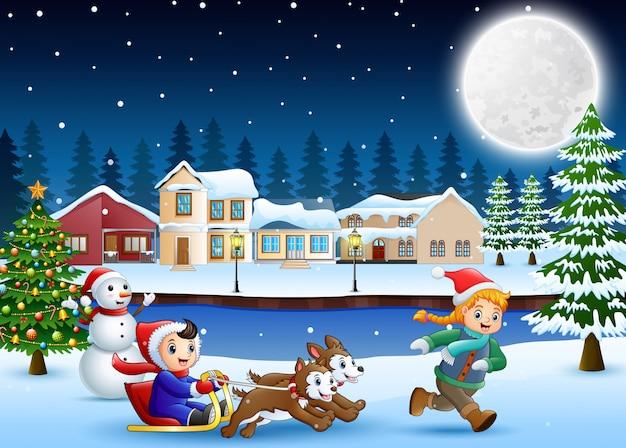 Karikaturjungenreitschlitten auf dem schneienden dorf mit laufendem kind