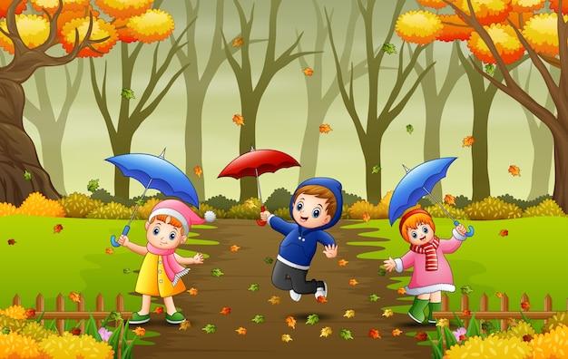 Karikaturkinder, die regenschirm im herbst halten