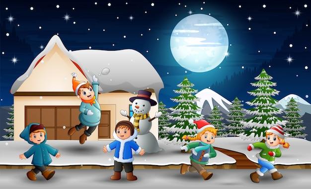 Karikaturkinder, die vor dem schneienden haus spielen