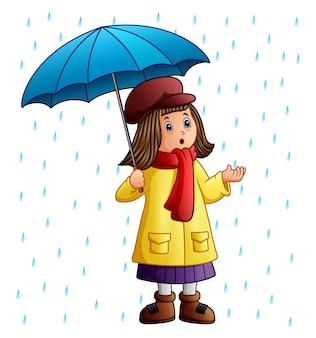 Karikaturmädchen mit dem regenschirm, der unter den regentropfen steht