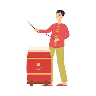 Karikaturmann, der rote chinesische trommel im traditionellen festkostüm spielt - glücklicher lächelnder junge, der trommelstöcke hält. illustration auf weißem hintergrund.