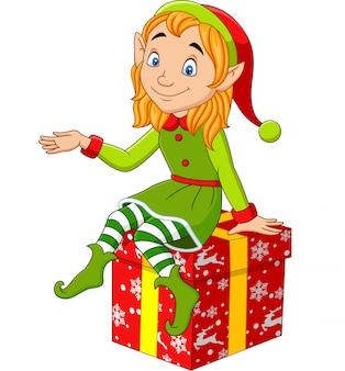 Karikaturweihnachtselfe, die auf dem geschenk sitzt