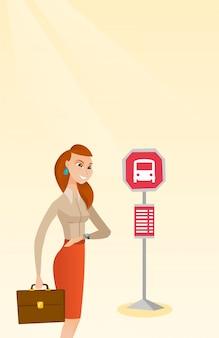 Kaukasische frau, die auf einen bus an der bushaltestelle wartet.