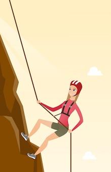 Kaukasische frau, die einen berg mit seil klettert