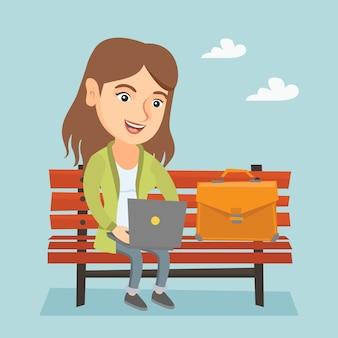 Kaukasische geschäftsfrau, die an dem laptop im freien arbeitet